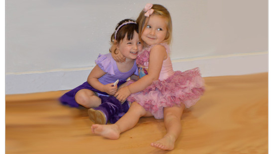 Two little ballerinas sitting on the floor hugging.