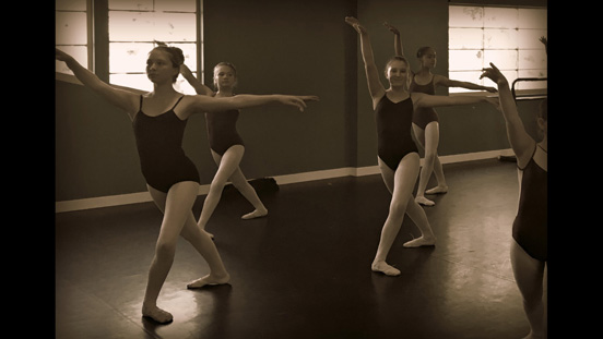 Image of ballerina dancers lunging, posing in the Performing Arts Academy dance studio.