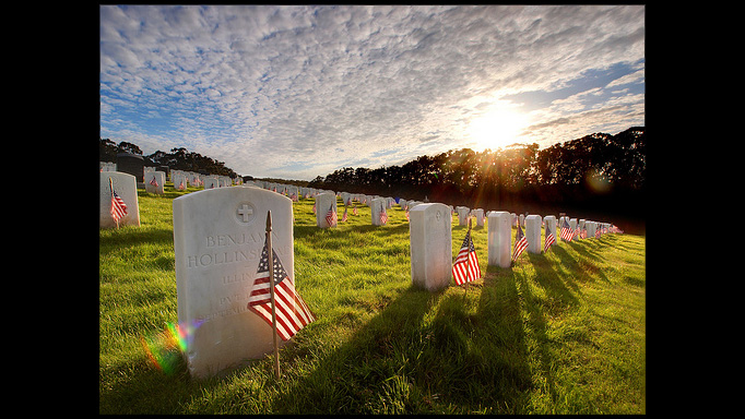 Flags in front of tombstones on a grassy hill in the sun.