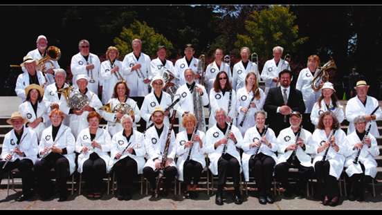 The Las Gallinas Valley Sanitary District Non-Marching Band posing in white coats holding their instruments.