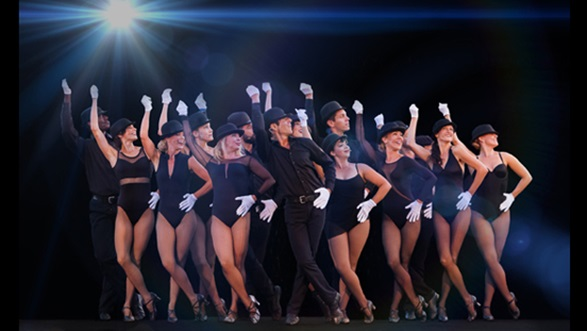Group of men and women in black leotards and hats with white gloves, posing with one arm in the air snapping their fingers.