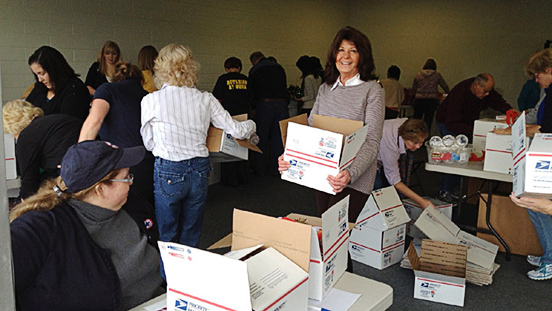 Supervisor Judy Arnold in a room with people packing postal boxes.