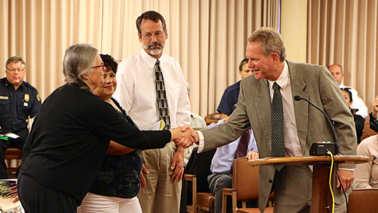 Supervisor Steve Kinsey shaking hands with audience members at a meeting.