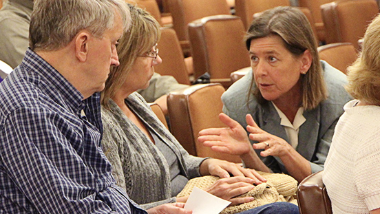 Supervisor Katie Rice speaking with 2 people at a Board Of Supervisors meeting.