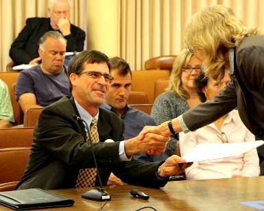 David Lewis shakes the hand of Supervisor Kate Sears during a 2014 Board of Supervisors meeting.