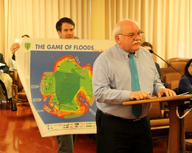 Jack Liebster speaks to the Board of Supervisors about the 'Game of Floods' as cohort Alex Westhoff holds up the game.