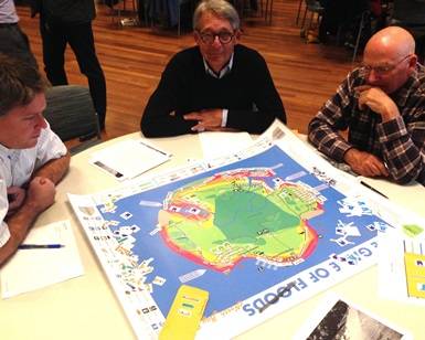 Three men play the Game of Floods board game
