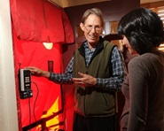 A man from the BayREN home energy program points to a thermostat as he talks with a female homeowner.