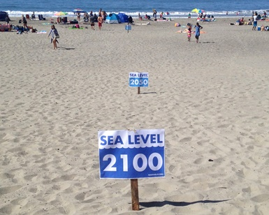 Signs in the sand at Stinson Beach show where expected ocean levels will be in 2050 and 2100.