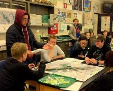 Students at Tamalpais High sit around a table and look at a map showing future sea-leve rise patterns.