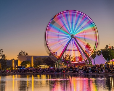 An illuminated ferris wheel spins at the County Fair, with the reflection of the lagoon in the foreground