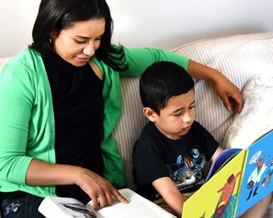 A woman reads a book with her arm around a young boy as he reads his own book.