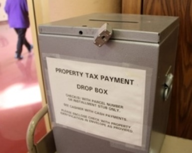 A silver box sitting in a Civic Center office has a sign that says Property Tax Payment Drop Box