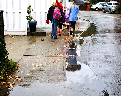 McAllister Avenue is shown with puddles in the gutter overflowing to the sidewalk and children walking to school in the background.