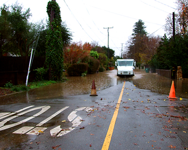 A mail delivery truck navigates a flooded roadway in Novato.
