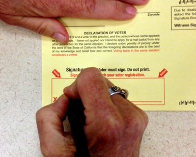 A close-up of a hand with a pen, depicting a person signing a ballot.