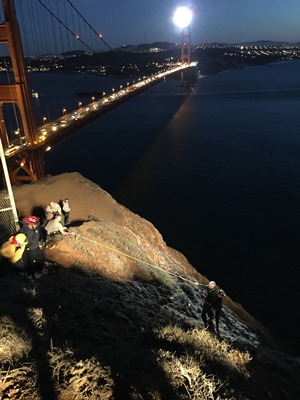 A man and a firefighter on the right get pulled up to safety by other rescuers on the left via a rope line, with the Golden Gate Bridge in the background.