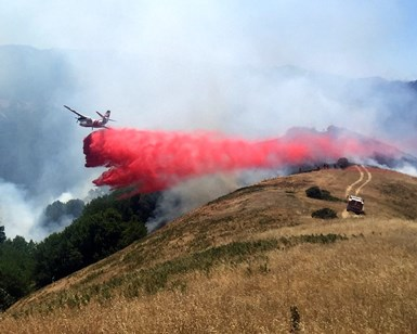 An airplane from Cal Fire lets loose on a load of fire retardant as if flies over the fire near Kent Lake.