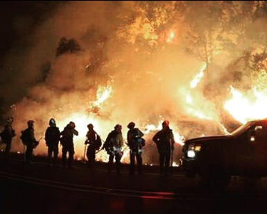 A nighttime view of Marin County firefighters silhouetted against flames at the Valley Fire in Lake County.