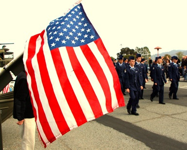 An American flag flaps as Junior ROTC cadets walk by during a Veterans Day event in 2013.