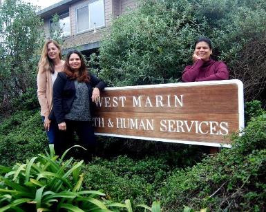 Three women who work at the West Marin Service Center stand next to the large wooden sign outside the building's door.