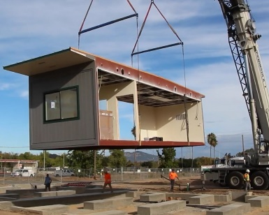 A large crane hoists a modular building into place at the new site of the South Novato Library.