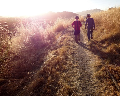Two young boys walk on an unpaved path toward the sunset