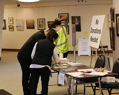 Several county employees sign in at a registration table at the wildfire evacuation shelter.